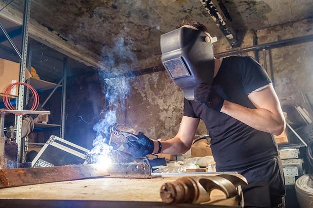 金属溶接機を醸造する若い強い男性の溶接工