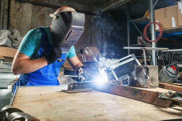 Молодой силач-сварщик сваривает сварочный аппарат для металла в старой темной мастерской,