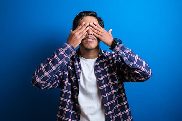 어린 학생은 파란색 배경에 양손으로 눈을 감았다