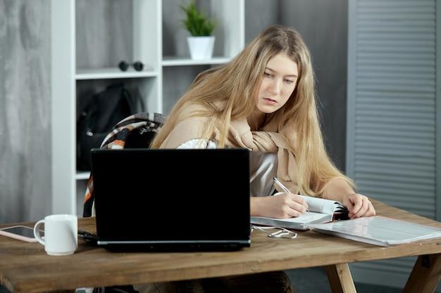 어린 학생이 집에서 숙제를 하고 노트북이 있는 테이블에 앉아 있다