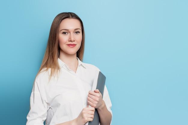 白いシャツを着た若い学生の女の子は、テキスト用の青い壁に手でフォルダーを保持しています。手でドキュメントペーパーでかわいい学生。オフィスの服のビジネスウーマン
