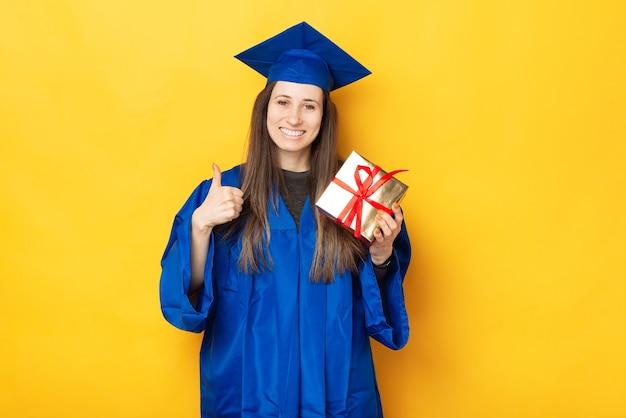 Молодая студентка улыбается в камеру, потому что получила свой подарок на выпускной