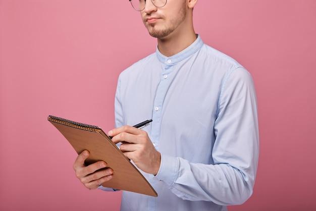 Молодой студент с коричневым флипчартом в одной руке и черной шариковой ручкой пишет