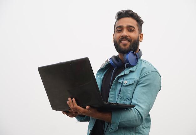 Молодой студент с концепцией образования ноутбука и наушников
