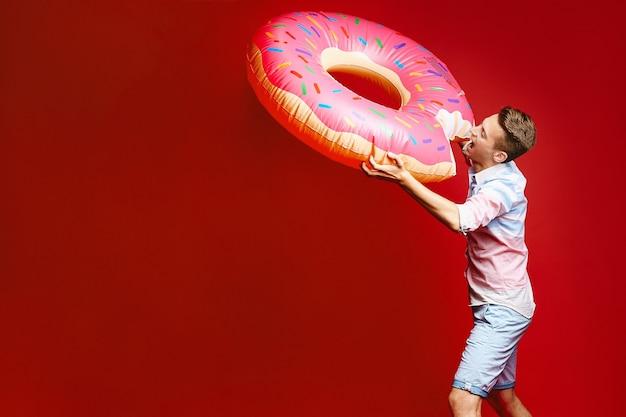 민소매 셔츠와 반바지를 입은 세련된 금발 남자가 풍선 도넛과 함께 포즈를 취하고 있습니다.