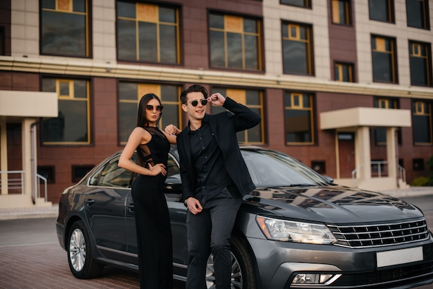 日没で車の近くに黒のスタイリッシュなカップルが立っています。ファッションとスタイル