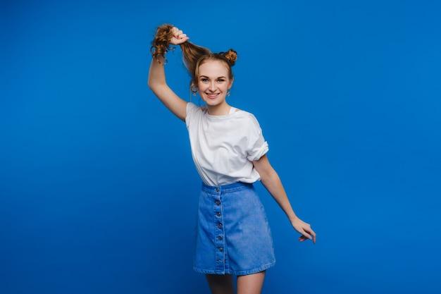 세련된 소녀가 파란색 배경에 머리를 당기고 모델은 긴 머리를 당깁니다.
