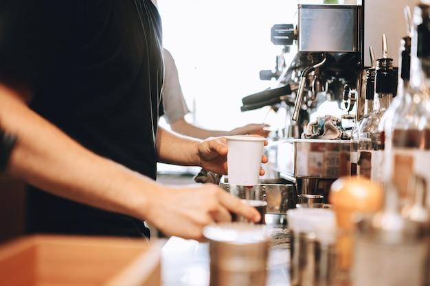 Молодой стильный мужчина в повседневной одежде варит кофе в современной кофейне. показаны руки и чашки. .