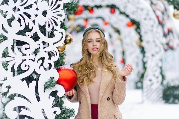 赤いクリスマスツリーの大きなボールを持つ若いスタイリッシュな女性お祝いのクリスマスマーケット