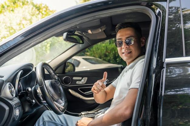 サングラスをかけた若い成功したアジアのビジネスマンは、高価な現代の車に座って、カメラを見て笑っています