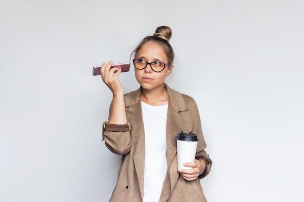 Молодая успешная блондинка держит белый бумажный стаканчик с кофе или чаем, слушая голосовые сообщения