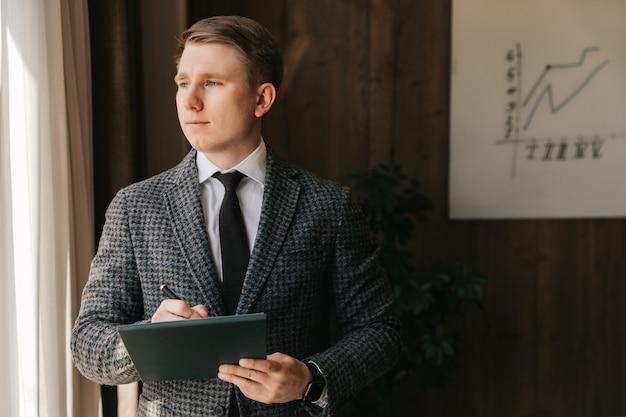 Молодой успешный бизнесмен и офисный работник со светлой кожей держит в руках папку с документами, стоит в своем офисе. мужчина работает в офисе, делает заметки на бумаге.