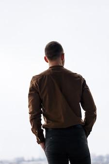 Молодой успешный бизнесмен-мужчина свободно стоит у большого окна и смотрит на город.