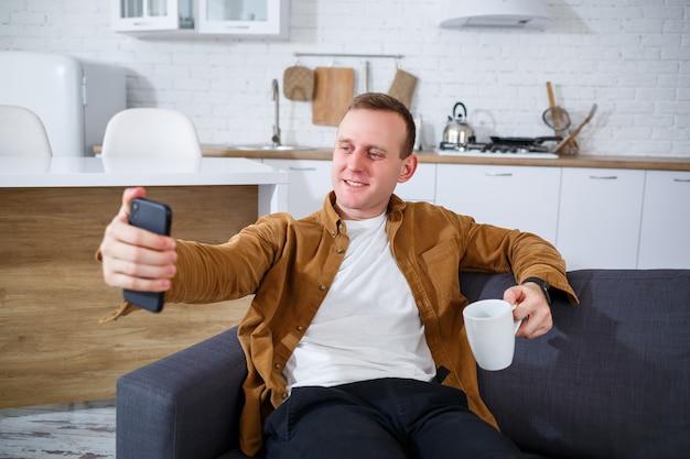若い成功した男が自宅のソファに電話を持って座って、ビデオリンクで話している。検疫中のリモートワーク。