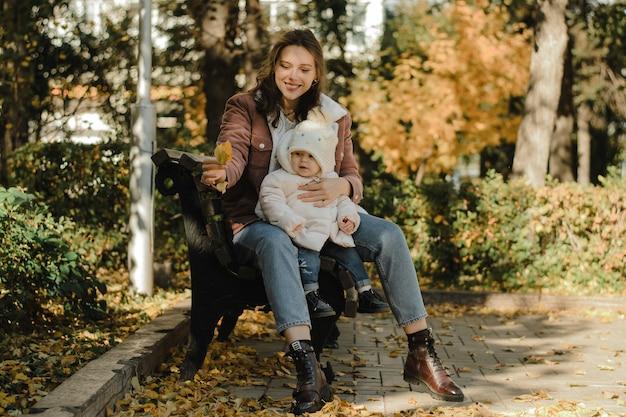 Молодая, милая мама обнимает свою дочь и показывает ей упавший осенний лист. мама и малыш сидят на скамейке в парке