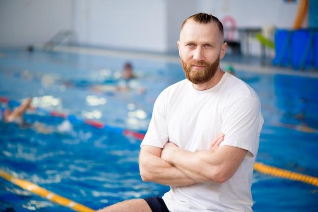 若い水泳コーチがスポーツプールの近くでトレーニングを見ています。