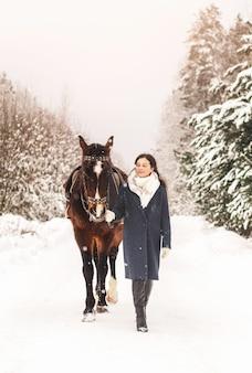 若いsymatic女の子は自然の中で冬に散歩馬を取ります。人間と動物の友情