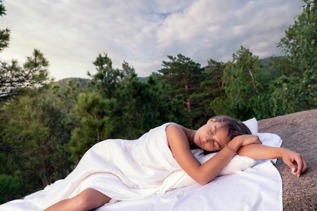 背景に対して山の真っ白なシートで寝ている若い日焼けした女の子