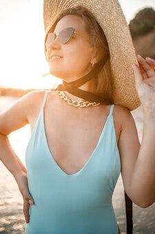 밀짚모자를 쓴 아름다운 수영복을 입은 그을린 젊은 여성이 모래가 있는 열대 해변에 서서 일몰과 바다를 바라보고 있습니다. 선택적 초점입니다. 바다로 휴가 개념