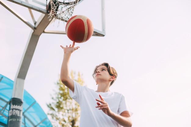 白いtシャツを着た若い10代のバスケットボール選手がバスケットボールコートに立っています
