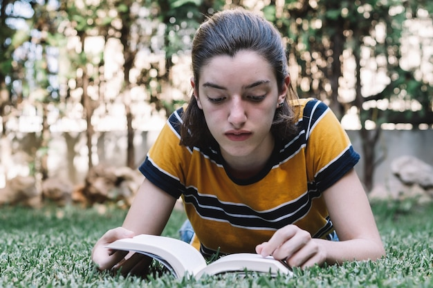 若い10代の少女は、屋外のノートの草を描きます。