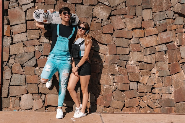 スケートボードを持った若いティーンエイジャーと、屋外でヘッドフォンを持ったガールフレンド。