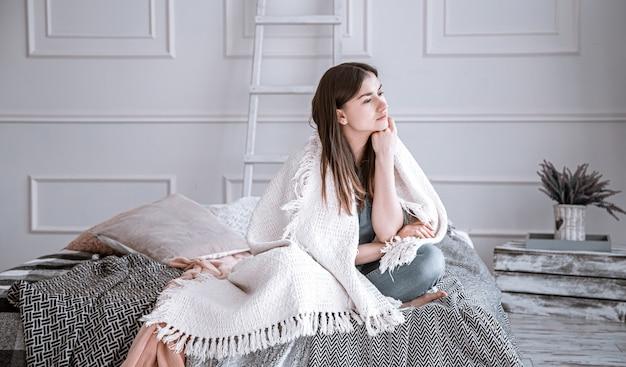 若い、思いやりのある女性は、悲しい気分で毛布で覆われた居心地の良い部屋のベッドに座っています。