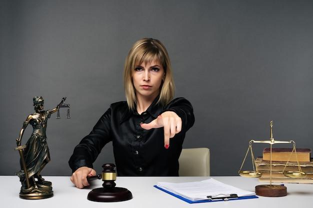 В своем кабинете работает молодая уставшая честная женщина-судья.