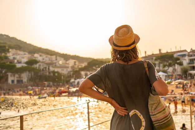 팔라프루겔 마을의 타마리우 해안에서 석양을 바라보는 젊은 관광객. 지중해의 코스타 브라바 지로나