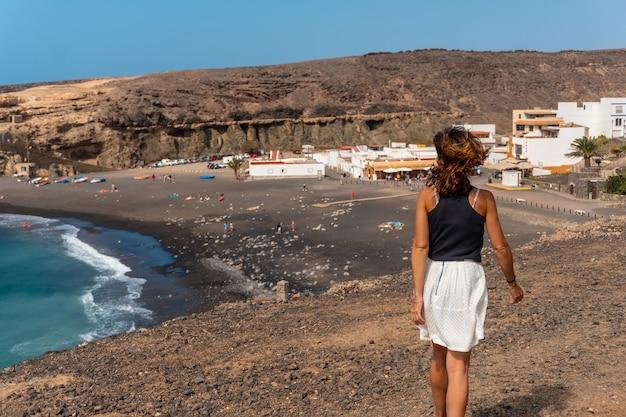 Молодая туристка на отдыхе на пляже аджуй, пахара, западное побережье острова фуэртевентура, канарские острова. испания
