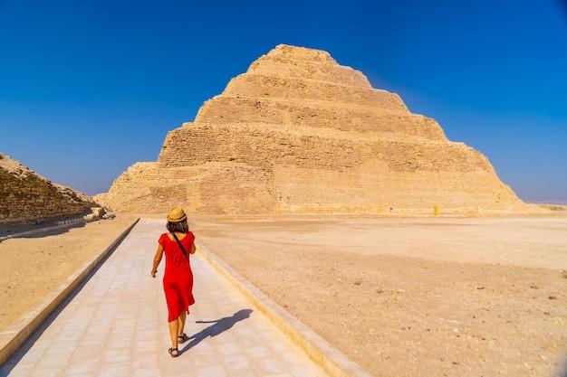 Saqqaraのdjoserの階段状のピラミッドで赤いドレスを着た若い観光客。エジプト。メンフィスで最も重要なネクロポリス。世界で最初のピラミッド