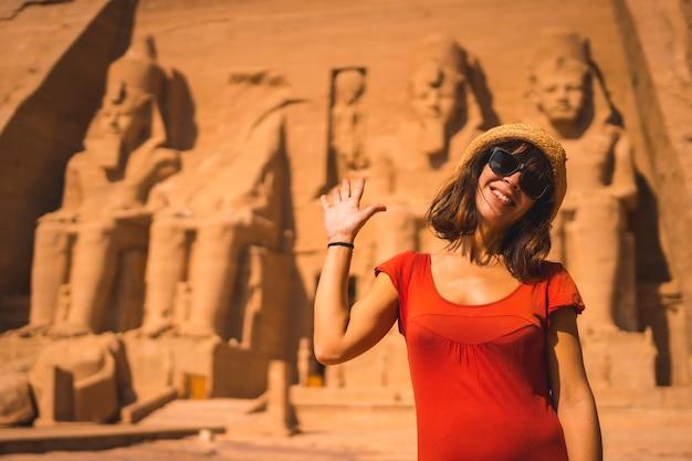 누비아의 이집트 남부 아부 심벨 사원에서 빨간 드레스를 입은 젊은 관광객