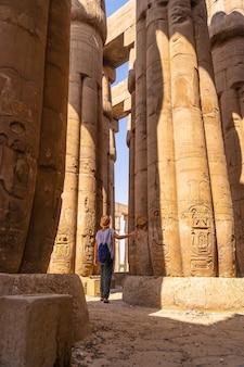 エジプト、ルクソール神殿の柱に描かれたエジプトの絵を見ている若い観光客