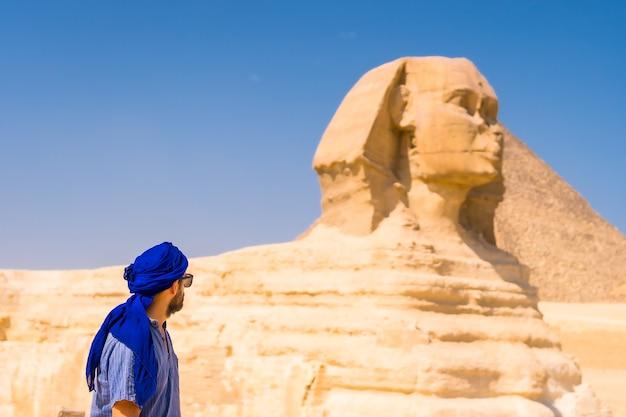 青と青のターバンに身を包んだギザの大スフィンクスの近くの若い観光客。そこからギザのミラミド、文化観光、そして多くの歴史があります。カイロ、エジプト