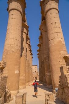 エジプトのルクソール神殿にあるエジプトの絵が描かれた貴重な柱の横にある若い観光客