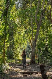 ホンジュラスのコパンルイナスの木々の中で美しい森の小道に若い観光客