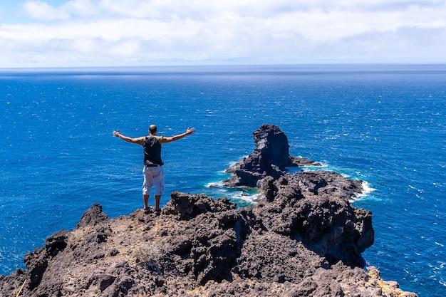 カナリア諸島のラパルマ島の北にあるブハレンの黒い砂のビーチに下りる崖の道にいる若い観光客。スペイン