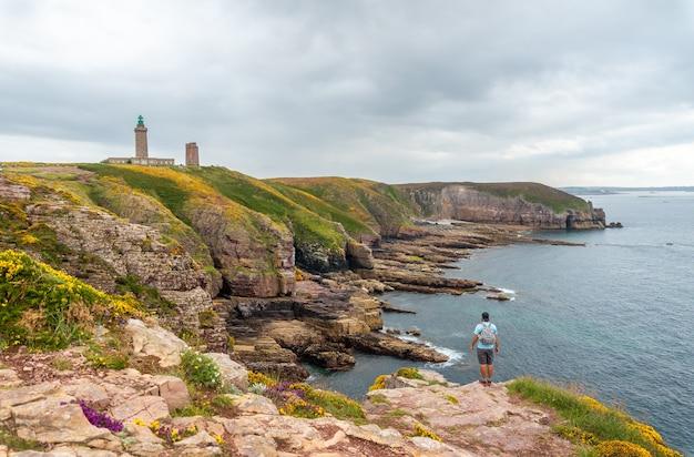 Молодой турист на побережье рядом с phare du cap frehel, это морской маяк в кот-д'армор (франция). на вершине мыса фрехеля