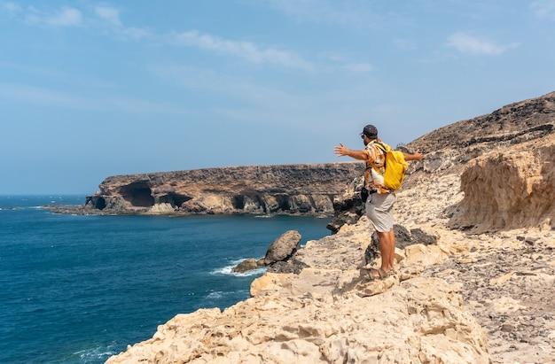 Молодой турист на тропе, направляющейся к пещерам аджуй, пахара, западное побережье острова фуэртевентура, канарские острова. испания