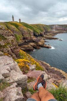 Молодой турист сидит на берегу рядом с phare du cap frehel, морским маяком в кот-д'армор (франция). на вершине мыса фрехеля