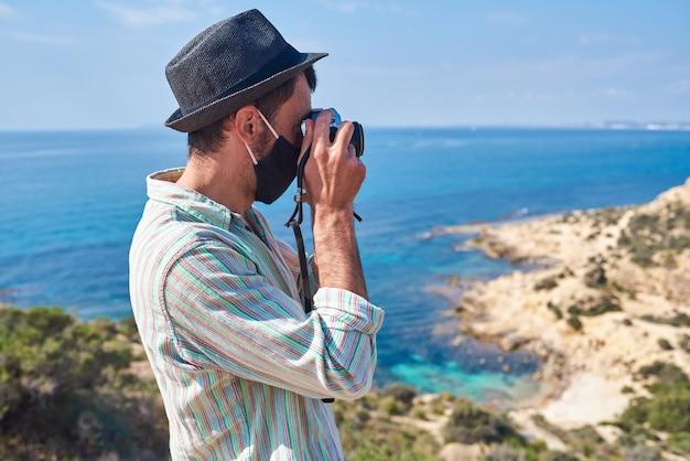 아름다운 색상으로 바다가 보이는 언덕 꼭대기에서 젊은 관광객이 사진을 찍습니다.