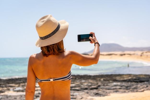 카나리아 제도 푸에르테벤투라에 있는 코랄레호 자연 공원의 모래 언덕 해변에서 사진을 찍고 있는 젊은 관광객. 스페인