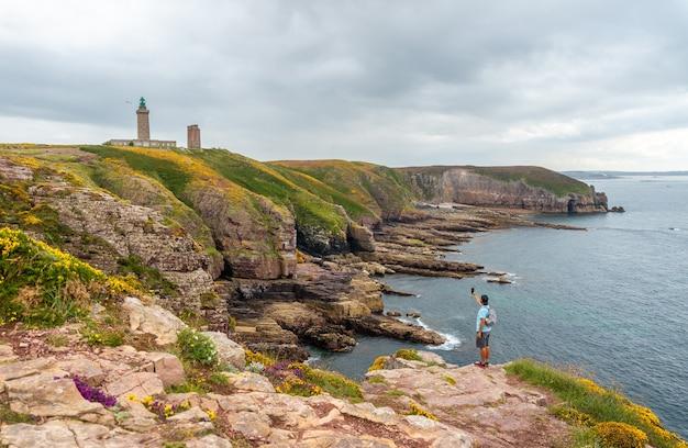 Молодой турист делает снимок на побережье рядом с phare du cap frehel, это морской маяк в кот-д'армор (франция). на вершине мыса фрехеля
