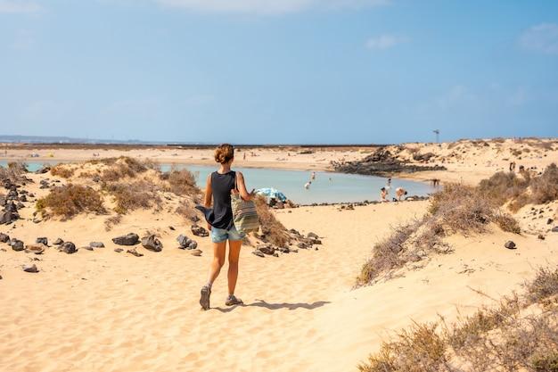 카나리아 제도 푸에르테벤투라 섬의 북쪽 해안 옆에 있는 이슬라 데 로보스의 라 콘차 해변을 방문하는 젊은 관광객. 스페인