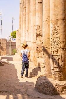 寺院を訪れ、エジプトのルクソール神殿の絵を見ている若い観光客