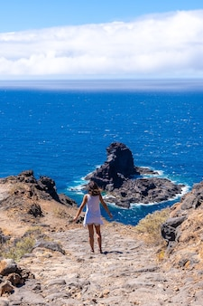 カナリア諸島のラパルマ島の北にあるブハレンの黒い砂のビーチに下りる崖の道を歩く若い観光客。スペイン