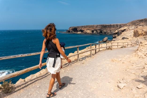 Молодой турист идет по тропе в куэвас-де-ажуи, пахара, западное побережье острова фуэртевентура, канарские острова. испания