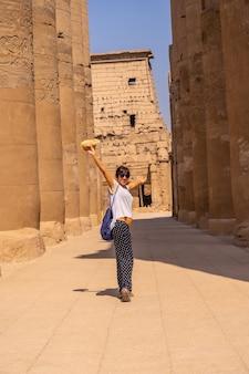 ルクソールのエジプトの神殿を訪れる帽子をかぶった若い観光客