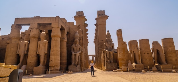 ルクソールのエジプトの神殿とその美しい柱を訪れる帽子をかぶった若い観光客