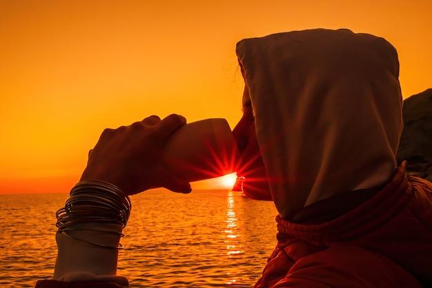 Молодая туристка держит чашку стакана для кофе, сидя на открытом воздухе и наслаждаясь восходом солнца над морем